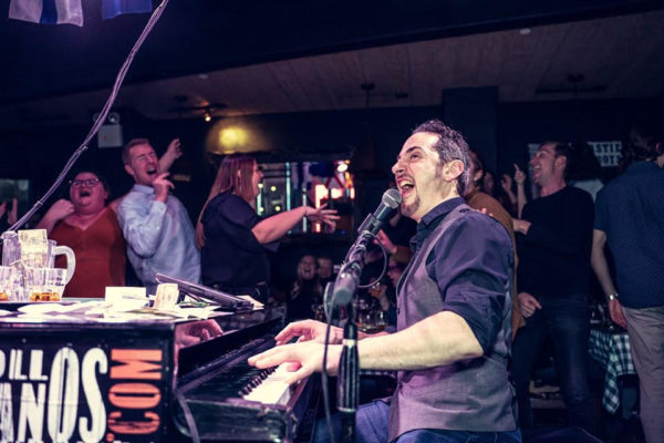 Piano man Mark Weiser singing and playing to a the crowd at a dueling pianos show.