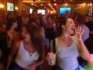 Two girls at a bachelorette's party dance in the foreground of the crowd at a dueling pianos show.